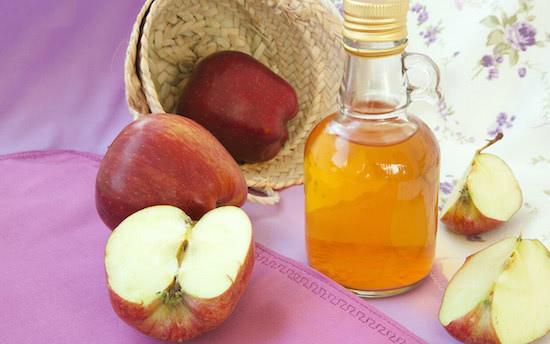 apple cider vinegar bottle and apple