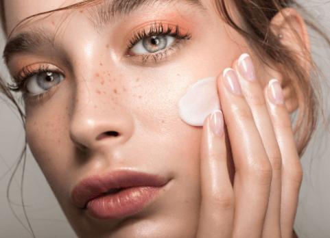 woman rubbing moisturizer on face